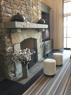 Fabulous stone fireplace . A little dried cotton and white hide ottomans lights up the space. Meridy King