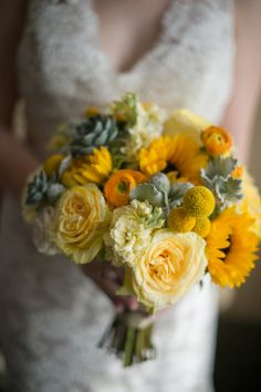 yellow themed bouquet with roses, sunflower, billy balls, dusty miller, and succulents.
