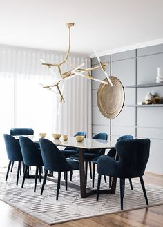 Velvet chairs and statement chandelier. For more, visit houseandleisure.co.za