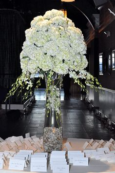 Superior Florist – Weddings – Escort Tables: Large mound of white Hydrangeas with draping Dendrobium orchids. Submerged, variegated Dendrobiums in clear, glass fluted vase with river rocks in base.