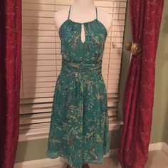 Loft Halter Dress Beautiful teal background,w/vibrant blues,lime green & navy floral design.Key hole at halter neckline,elastic on back.Cummerbund waist is ruched,fully lined.Both layers fully lined.Side zipper.Pic #4 shows snag on side of dress from front,not noticeable when dress is worn.Small snag at top of where zipper is.armpit to armpit 13.5 inches.Size 2.❌❌no trades❌❌ LOFT Dresses