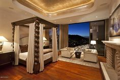 Luxurious master bedroom with a raised gold ceiling, unique four post bed, and seating area.    Source: http://www.zillow.com/digs/Home-Stratosphere-boards/Luxury-Bedrooms/