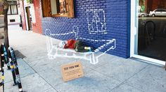 A Weingart Center volunteer curls up on the sidewalk, a chalk bedroom drawn around her. The street art's aim to is draw the attention of passersby to a nearby cardboard sign with directions for how to text donations to the nonprofit charity for the homeless