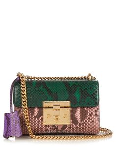 Gucci's Mini shoulder bag is crafted from glossy panels of python in rich jewel tones of emerald, pink, and purple. A gold-tone metal chain strap and lockable clasp elevate the look, while the supple suede-lined interior is perfectly sized for edited essentials. Watch it bring a little eclectic spirit to any look, day or night.