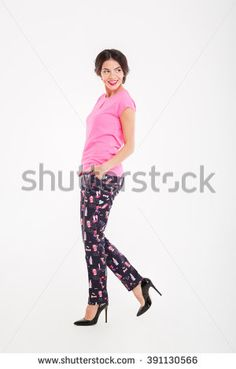 Full length of cute playful young woman standing and looking back over white background - stock photo