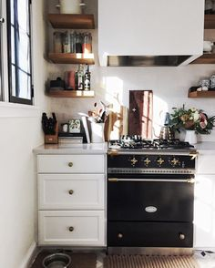 Kitchen goals. Love that black stove contrast with the white cabinets