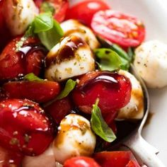 Close up of Caprese Salad with cherry tomatoes, baby mozzarella / bocconcini, basil leaves and dressed with a garlic-herb Caprese Salad dressing and drizzled with balsamic glaze.