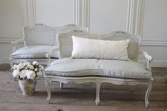 These have been painted in a oyster white with subtle distressed edges, and finished with an antique glaze. We have added a custom down cloud cushion with slip cover in our fog linen. The fog linen is a pale grey blue.