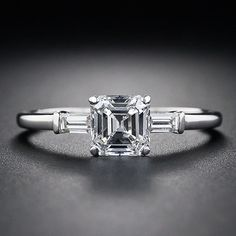 A bright-white and glistening square emerald-cut diamond - sometimes referred to as an Asscher-cut - gleams from between a pair of baguette diamonds in this classic, timeless and traditional estate engagement ring, crafted in platinum, circa 1930s.