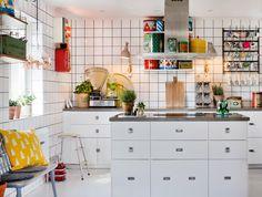 Vita helkaklade väggar, vita golv och bänkskivor av flytspackel med känsla av betong sätter stilen i detta industrikök.
