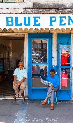Port Louis, Mauritius: A man reads his paper outside his shop in Port Louis.