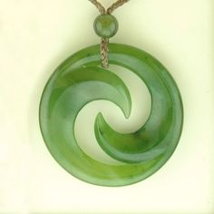 A double Koru Jade Maori pendant on a twine necklace. Double Koru: The stylization of the two unfolding fern fronds symbolizes the bonding within a family. As each frond unfolds to leave the protective circle, it reaches out for new life, new growth and so reflects the life cycle.