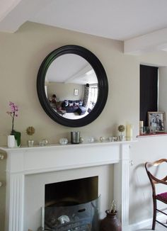 A well positioned mirror can do wonders for the home - adding light, space and interest. Here are 4 essential tips for hanging a round mirror above fireplace ideas 4 Essential Tips for Hanging a Round Mirror above a Fireplace - Omelo Mirrors Above Fireplace Ideas, Mirror Above Fireplace, Fireplace Lighting, Fireplace Wall, Living Room With Fireplace, Fireplace Surrounds, Black Round Mirror, Round Wall Mirror, Round Mirrors
