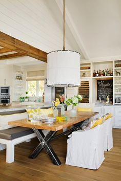 Beyond the secondary island is the dining table, which Lauren had cut down from a larger antique piece to fit the space and paired the reclaimed wood slab with a sleek steel frame. Just beyond the eating area, Eric designed a wet bar with a prep sink, wine fridge, coffeemaker, and ample glassware storage. When entertaining, Lauren uses the built-in chalkboard to highlight the evening's menu or specialty drink.   - HouseBeautiful.com