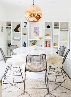 Dining space with a modern table, bronze pendant light and a Beni Ourain Rug