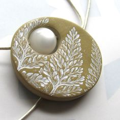Frost Fern Necklace Polymer Clay and Moonglow Bead Necklace.    Simple, charming fern fronds are impressed into pearly bronze polymer clay and painted a frosty white. The pendant is sanded and a glowing Moonglow bead is strung in the center. The pendant is strung for an asymmetrical effect, which is best seen in the last photo.    The pendant comes strung on a 1mm pearly white leather cord with a bead/loop/toggle closure. The toggle bead is made from the center circle that was removed to…