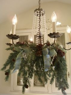 Don't leave your chandelier out of the party! It can be decorated for Christmas, too! With a little bit of garland & some ribbon, your chandelier can look as beautiful as this one.