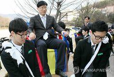 Estudiantes surcoreanos llevando a sus profesores en palanquín.