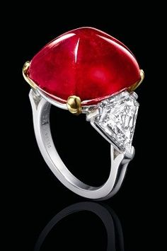 *IMPORTANT RUBY AND DIAMOND RING, BULGARI Centring on a sugar loaf cabochon ruby weighing 27.67 carats, flanked on each side by a shield-shaped diamond together weighing approximately 3.00 carats, mounted in platinum and 18 karat yellow gold, signed.