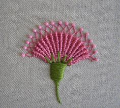 "I ❤ embroidery . . . TAST whipped spiderweb- Here is a version of whipped spiderweb - a carnation, or ""pink"". The cool thing about this flower is that each spoke is not just a straight stitch, it is a long and skinny chain stitch. Once the whipping is done, the sides of each chain are pulled together to form the diamonds at the top. This is from Jane Nicholas' book Stumpwork Embroidery. ~By LinMoon, Purple Fan: May 2007"