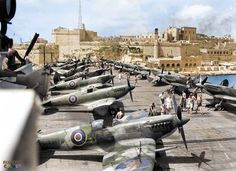Supermarine Seafire L.IIIs of RNAS 808 Squadron on the deck of the escort aircraft carrier HMS Khedive (02), entering the Grand Harbour of Valletta in Malta. July 1944. (Colourised by Royston Leonard)
