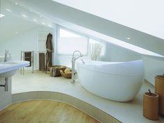 <p>Die freistehende Badewanne wurde ebenfalls auf dem Podest platziert. Durch das darüberliegende Dachschrägenfenster kann der Blick uneingeschränkt in die Ferne schweifen. Die hellen Materialien und die großzügige Raumaufteilung lassen den Raum luftig und großzügig wirken.</p>