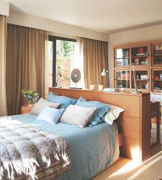 Dormitorio con cabecero de teca a media altura que divide con el rincón de trabajo