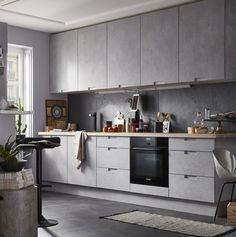 Avec ses façades effet béton gris nuancé, cette cuisine ouverte sur le salon évoque l'esprit loft avec une allure chic et épurée.  ...