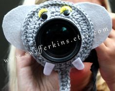 For a photographer who works with children on a regular basis this camera buddy can help you capture the childs attention and look at the camera.  This crochet frog lens critter will fit over several different sizes of lenses. (If you need one larger then normal, let me know and I can make a larger one) Made with an elastic in the middle it stretches nicely and fits your lens snug. Wiggly eye color can vary.  Shown photographed on a regular 28-75 mm lens if you think you need a larger one…