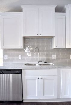 An example of gray subway tile in a white kitchen with white grout. Smoke Gray glass subway tile, white shaker cabinets, pull down faucet - gorgeous contemporary kitchen. Kitchen Cabinets Decor, Cabinet Decor, Kitchen Redo, New Kitchen, Copper Kitchen, Rustic Kitchen, Kitchen Storage, Cabinet Ideas, Awesome Kitchen