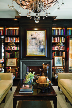 Bespoke shelving in this Dallas apartment; design by architect Ralph Duesing and decorator John Bobbitt. I love the black walls juxtaposed with the brightly colored books.
