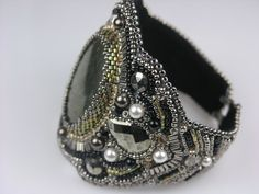 """pyrite cabcohon. It's surrounded with pearls, two faceted pyrite teardrop cabochons, Swarovski crystals, faceted nailheads, and hundreds of tiny glass beads, bugles and discs. The inside of the cuff is black ultrasuede. It measures almost 3"""" wide at its largest center and tapers down to a comfortable 3/4"""" wide near the clasp."""