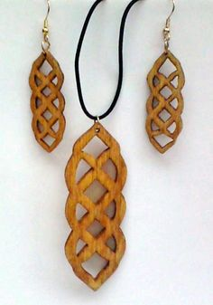 Pendant & Matching Earrings #5 Long style Celtic design – approx. 1/8″ Baltic birch material. Pendant is approx. 1 1/4″ x 3 1/2″ stained golden oak. Earrings are approx. 3/4″ x 2″ stained identical to pendant. Necklace is black elastic material. Earrings have gold filled ear wires for use with pierced ears. All pieces are sealed with clear polyurethane. Different color stains can be used. Material not laser cut.