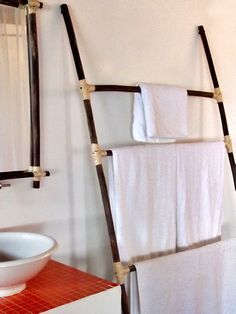Tropical-Style Towel Rack    Leaning a ladder against the wall is an unexpected way to hang towels. Designer Luis Caicedo chose this handmade tropical-style ladder because it doesn't take up a lot of room, and the material is carried through to the framed mirror for a unified look.
