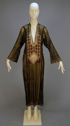 EGYPTIAN ASUITE TUNIC, Black cotton net with hammered silver decoration, the front slit with heavy banding on a bib of stylized leaves with diamond medallion, overall striped pattern with geometric trim to shoulder, sleeve and hem. Arab Fashion, 20s Fashion, Vintage Fashion, Modesty Fashion, Sporty Fashion, Fashion History, Vintage Style, Fashion Women, Winter Fashion