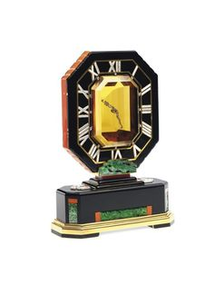 """An Art Deco Topaz, Jade, Coral And Enamel """"Mystery"""" Clock, by Cartier. Circa 1927."""