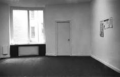 """""""January 5-31, 1969"""" - curated by Seth Sieglaub, 44 East 52nd Street, NY, 1969, with work by Douglas Huebler (papers on the windowsill), Lawrence Weiner (stain on the rug near window), Robert Barry (labels on wall near the door) and Joseph Kosuth (newspaper on wall)"""