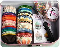 Nice idea for a gift - cupcakes, sprinkles + cake accessories all done up in a pretty box.