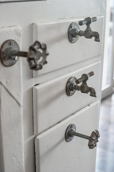 Antique metal knobs and spigots serve as unexpected drawer handles fashioned onto the baker's pantry and complete the vintage story in the kitchen.