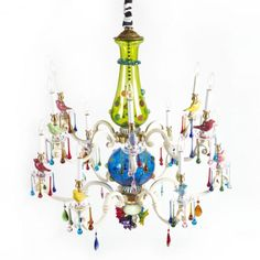 Like the branches of a tree in spring, our Merrifield Chandelier is adorned with a dozen colorful ceramic birds, handcrafted here in Aurora. Multicolored crystal prisms and wands, and a crystal bobeche, decorate each cast aluminum arm, antiqued white with touches of gold. The central glass globes and flowers, and the spectacular flowers at the base, are mouth-blown by a nearby artisan. The chain is covered by a black and white striped chintz cord cover for that added touch of whimsy.