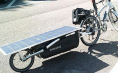 Biycle trailer with solar panel charges electric bike
