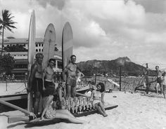 This classic photograph taken on Waikiki Beach during WWII features Duke Kahanamoku and others displaying trophies while apparently promoting an upcoming surfing or paddling competition - Note the barbed wire fencing in the background, the only visible sign of wartime conditions.