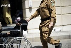 SAUDI ARABIA, MINA : A Saudi policeman pushes a wheelchair with an  injured pilgrim outside an emergency hospital following a deadly  stampede in Mina, near the holy city of Mecca, on the first day of Eid  al-Adha on September 24, 2015. At least 310 people were killed and  hundreds wounded during a stampede at the annual hajj in Saudi Arabia,  in the second tragedy to strike the pilgrims this year. AFP  PHOTO/MOHAMMED AL-SHAIKH