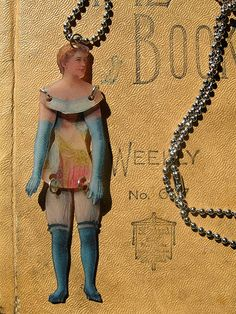 Art Doll Necklace in Blue. Created from shrink plastic and coated to protect it. Torso was hand cut from a scanned vintage label that was printed on shrink plastic as well. Arms and legs are jointed so she moves and dances as you wear her.