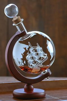 "Embrace your love of travel, adventure and whiskey with these stunning, mouth blown, lead-free glass decanters. Your guests will admire the artfully detailed antique ship encased in the etched globe decanter. Etched globe lead-free glass Detailed antique ship encased in the decanter Mahogany stained wood display Dimensions: 10"" H X 4- 1/2"" W X 6"" D Capacity: 35 oz. #bourbonandboots"