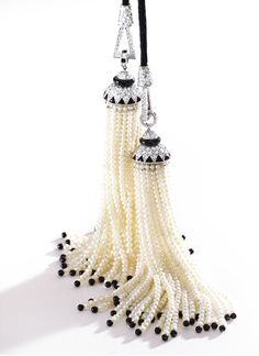 PLATINUM, DIAMOND, ONYX AND SEED PEARL DOUBLE TASSEL NECKLACE.  The tassels composed of seed pearls and onyx beads, capped with round and single-cut diamonds and onyx segments, the necklace composed of black silk cord accented by plaques set with round and single-cut diamonds and onyx rings, total diamond weight approximately 9.40 carats, length 20 inches.