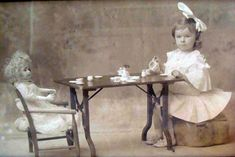 beautiful photo of a lovely young girl have tea with her bisque doll.
