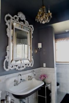 I love the mirror, chandelier and dark walls in this bathroom.