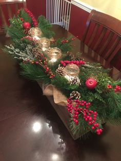 Wooden box centerpiece with greenery, berries, pine cones, burlap, mason jar candles for Christmas.