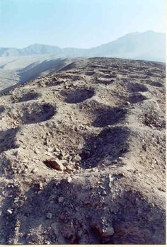 Unexplained Band of Holes near Pisco Valley in Peru. These strange holes, stretching for a mile over uneven mountain terrain, were here for so long that the local people have no idea who made them, or why. There are eight holes spanning 24 meters in width, marching in repetitive uniform fashion, from the Pisco Valley rolling over a mile through mountain terrain — finally disappearing in the misty mass of Peru.